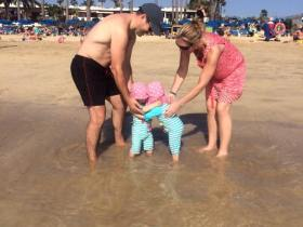 Twins playing in the sea on the beach with their mum and dad