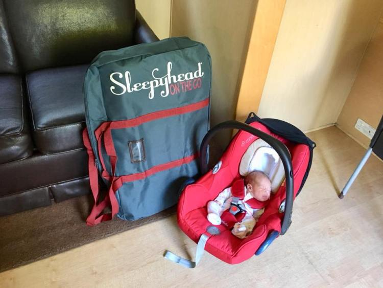 Sleepyhead in a travel bag with baby asleep in a car seat
