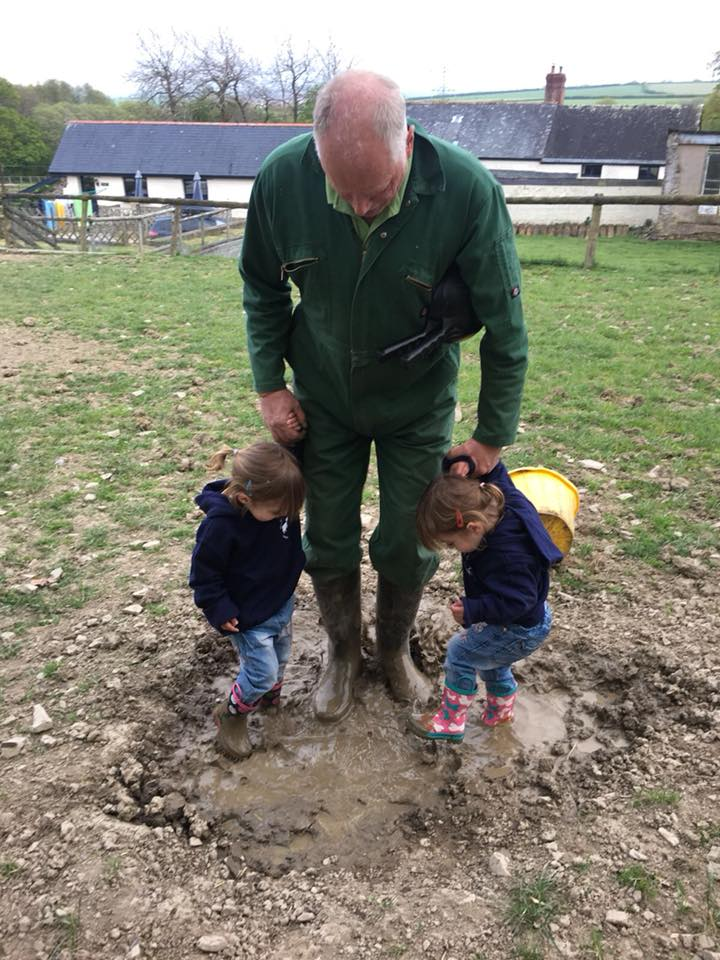 twins jumping in a muddy puddle with farmer