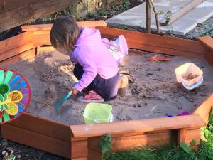 child sitting in the sandpit playing with the sand