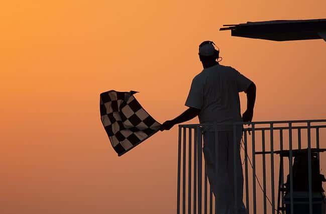 Mann schwenkt eine Zielflagge