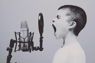 Kind singt überschwänglich in ein Mikrofon