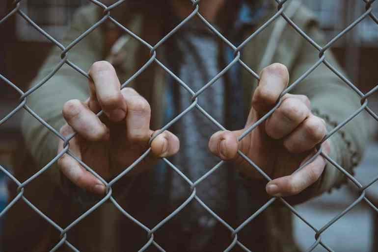 Mann steht hinter einem Zaun