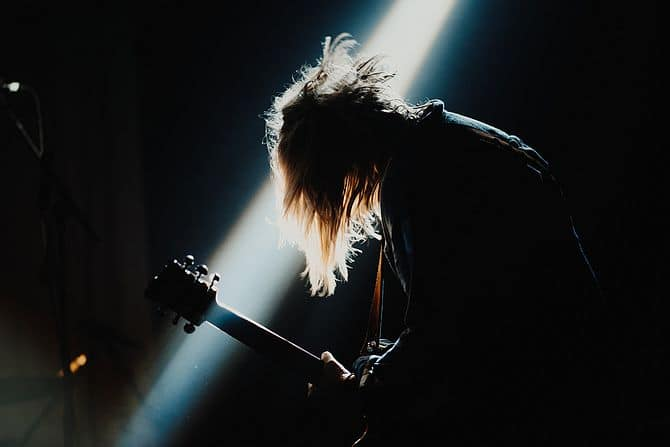 Mann mit Gitarre auf dunkle Bühne