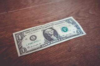 1 Dollar Schein liegt auf einem Tisch