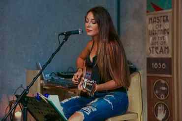 Hübsche Sängerin sitzt mit einer Gitarre auf einem Stuhl