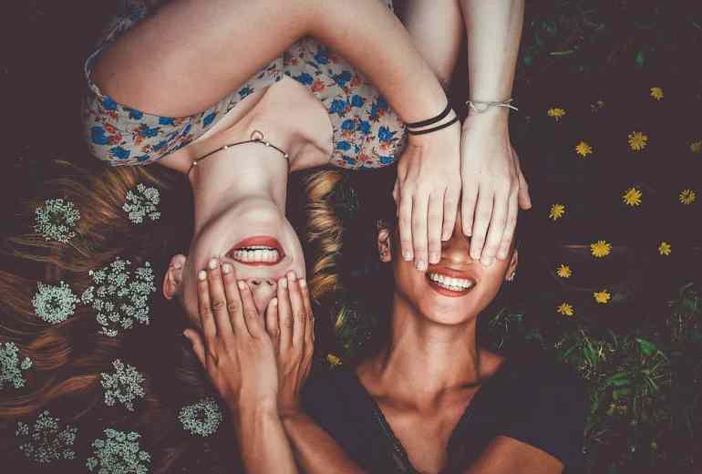 Zwei Freundinnen halten ihre Augen zu