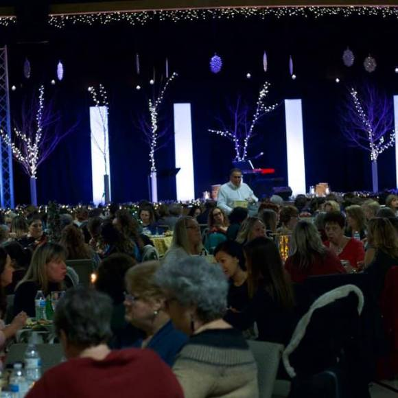 panoramic shot of Poplar Creek's Worship Center during the Christmas Tea showing women sitting around tables eating and talking