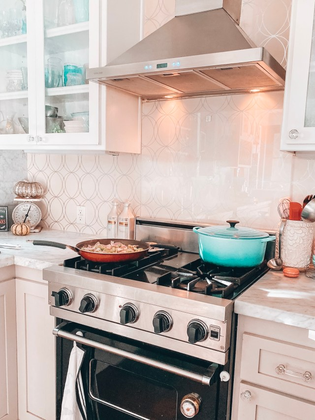 Blue Le Creuset dutch oven in white kitchen with metallic glam wallpaper | Poplolly co