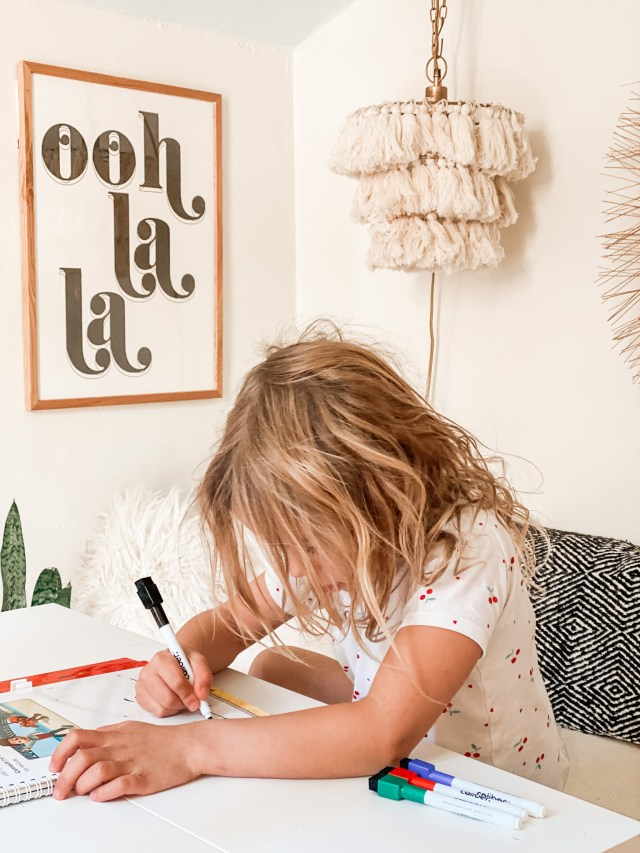 girl writing at her desk with markers in a neutral room with fringe lamp behind her | Poplolly co