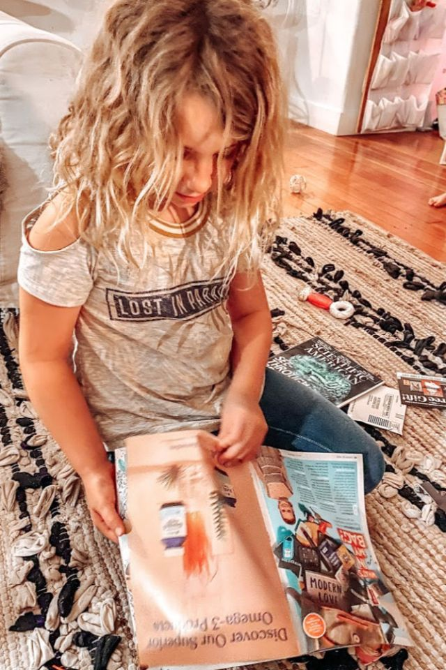 My daughter Violet Mae looking through magazines to find inspiration for her vision board | Poplolly co