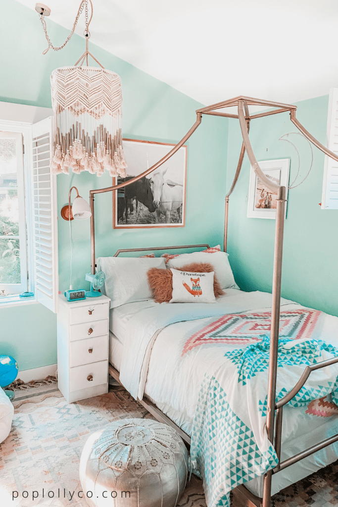 Turquoise boho girls room with macrame anthropologie chandelier, rose gold canopy bed and black white horse picture | Poplolly co