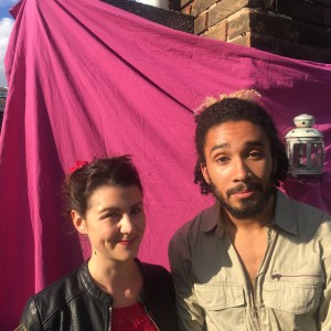 th'sheridans - Julia Oetli and Adam Sherif standing in front of a bright pink cloth backdrop