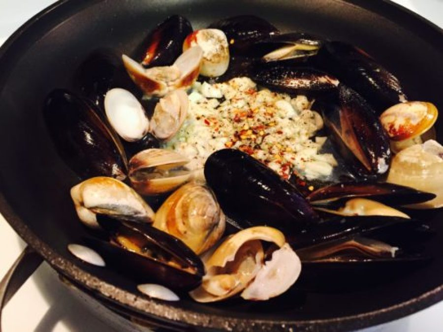 Clams and mussels added to pan with garlic and oil.