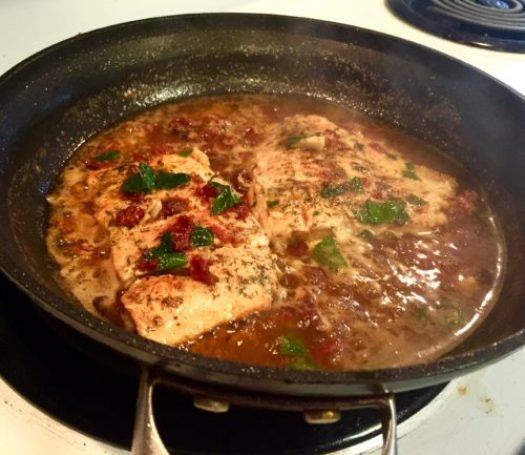 Salmon fillets heating up in sauce
