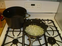 Water Boiling, Onions & Garlic Cooking in Olive Oil