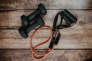 Workout weights and resistance bands on wooden surface