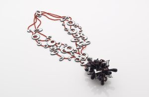 """Heavy Bassline (Stockholme Syndrome) Necklace : based on a fast drop D bassline in Muse song """"Stockholm Syndrome"""". Airbrushed polymorph and composite board with garnet and carnelian beads."""