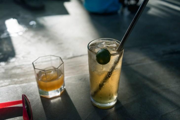 w mniejszej szklance miodowy rum, natomiast w większej drink na bazie lokalnego rumu i Sprite'a z calamansi