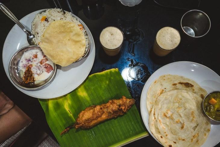 po lewej Biryani przykryte chlebkiem pappadam z podaną obok raitą, na środku papryczka smażona w cieście, a po prawej chlebek paratha podany z ziemniaczaną masalą