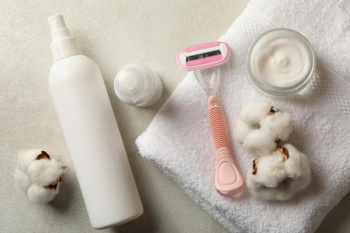 Shaving accessories and other feminine hygiene products on white table, top view