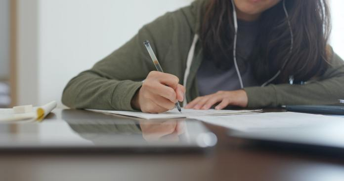 Woman do revision with cellphone at home
