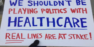 Stop playing politics with healthcare protest sign aimed at Sen. Tm Cotton. Photo from @doghouse on Twitter