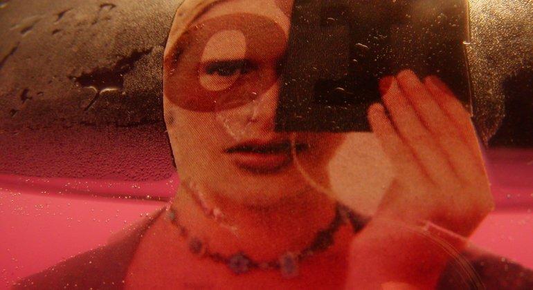 Kobieta przeglądająca się w lustrze w wesołym miasteczku