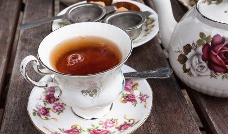 Filiżanka czarnej herbaty oraz porcelanowy czajniczek do parzenia