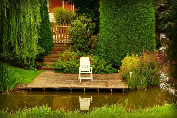 Zadbany ogród z tarasem wypoczynkowym i oczkiem wodnym