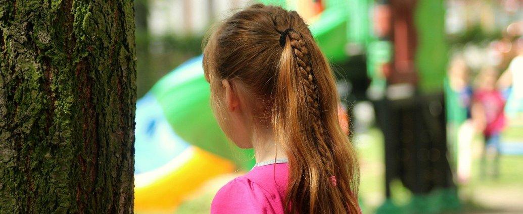 Nieśmiała dziewczynka stoi z dala od rówieśników