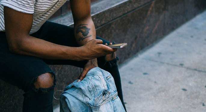 man using smartphone and holding jeans