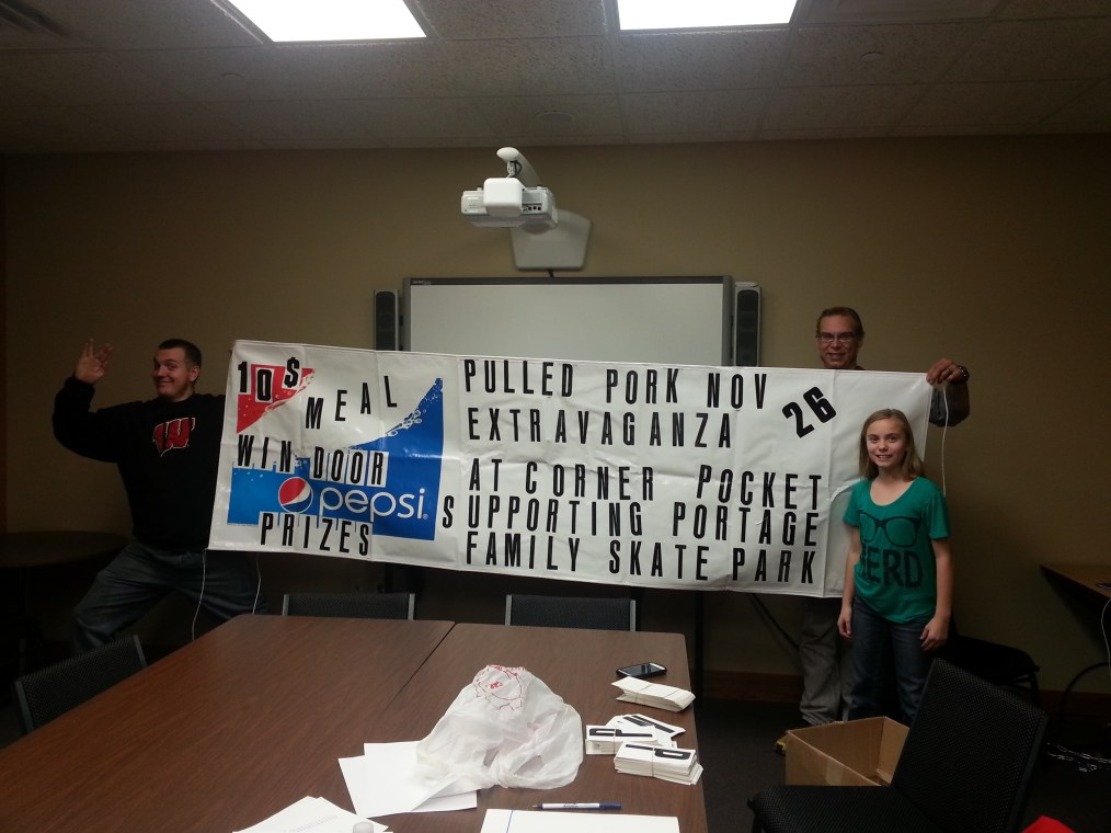 Sterling, Todd, Mariya putting the finishing touches on one of the event banners.