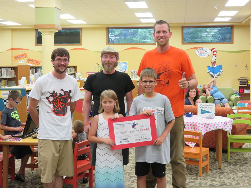 The winning charity, The Portage Family Skate Park, is represented by Kyle Little, Andrew Tamminga, and Jared Pierson. Reader, Ally Saloun and her brother (and teen volunteer) Jeremy Saloun, present a check for $200.00.