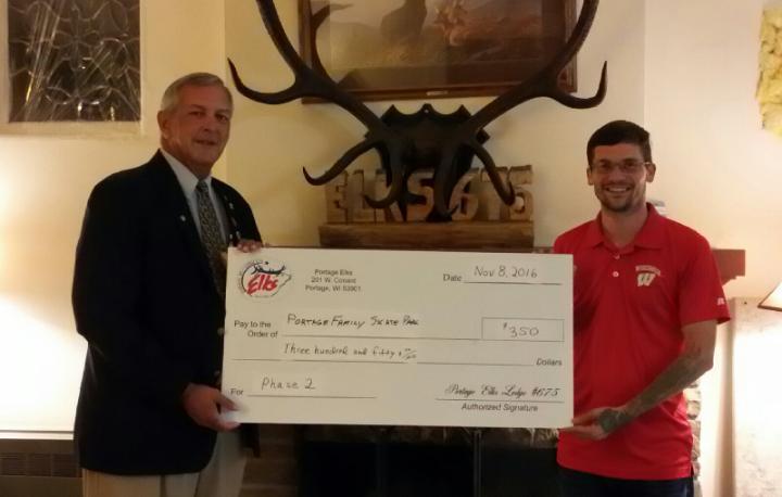 Matt Gorsuch chapter president of the Elks Lodge #675 awards president Kyle Little of the Portage Family Skate Park a check for $350.