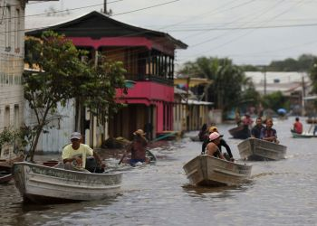 People pass on their boats through a street flooded by the rising Solimoes river, one of the two main branches of the Amazon River, in Anama, Amazonas state, Brazil May 13, 2021. Picture taken May 13, 2021. REUTERS/Bruno Kelly