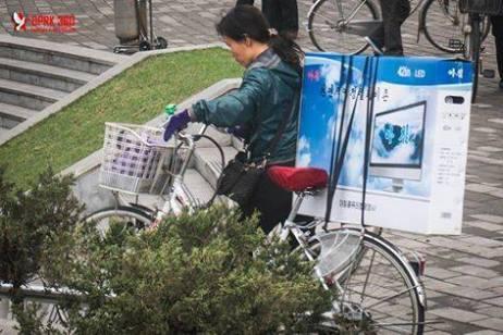 Cena comum na RPDC: cidadã norte coreana levando uma telvisão recém comprada para casa numa bicicleta. Algo incomum no Brasil devido as novas condições de segurança.