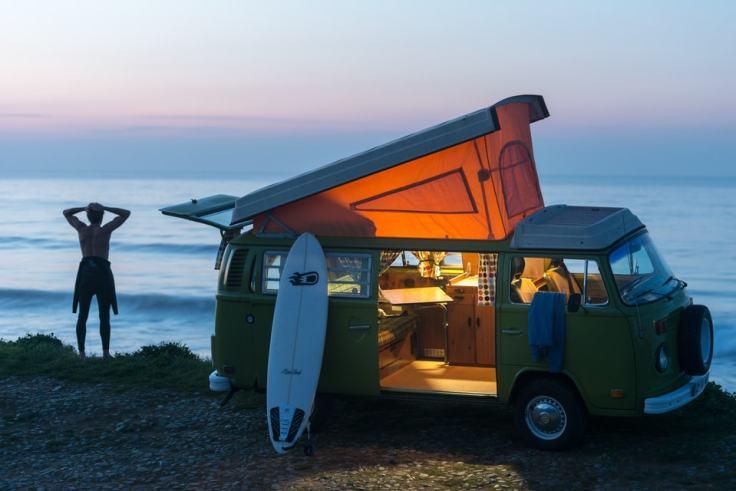 Erquy, surfeur et volkswagen combi 1976 sur la plage de Saint-Pabu de nuit au coucher du soleil.