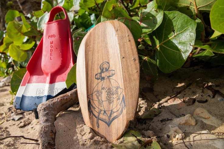 Sur une plage, une des handplanes en bois reposant contre un buisson avec une palme bleu, blanche et rouge.