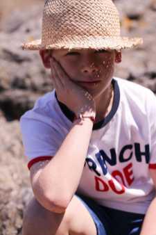 Enfant avec un chapeau de paille qui profite de l'été à la plage