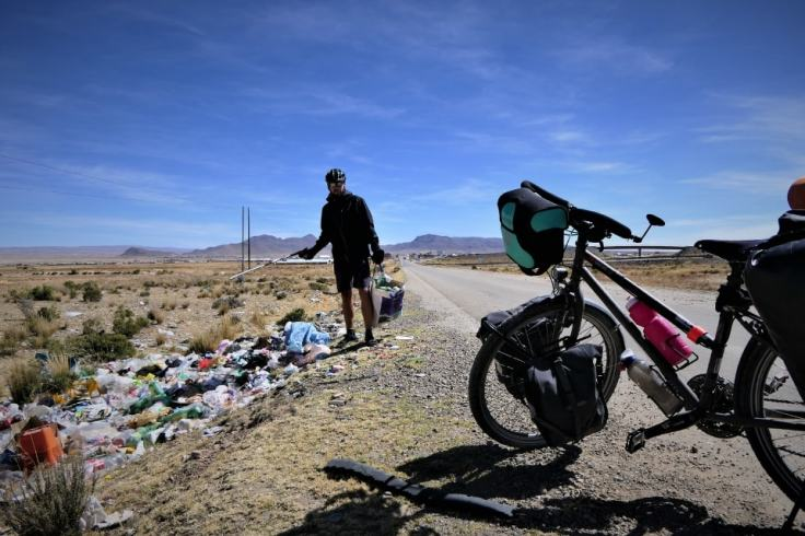 Promeneur à vélo qui s'arrête sur le bord de la route pour ramasser les déchets