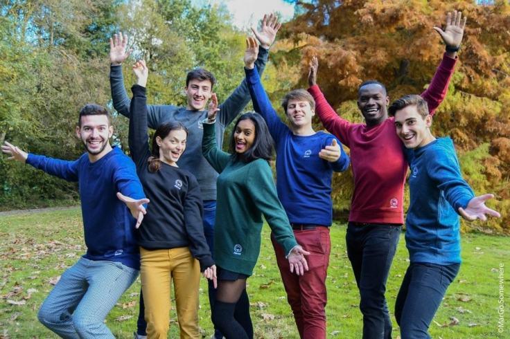 Groupe de jeunes amis qui met les mains en l'air