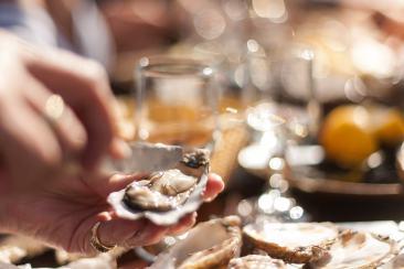 Une femme s'apprête à déguster une huître fraîche.