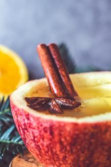 Pomme évidée remplie de cidre chaud, bâton de cannelle et fleur de badiane