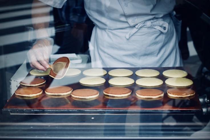 Un cuisinier prépare des hirams plattars suédois à travers une vitrine.