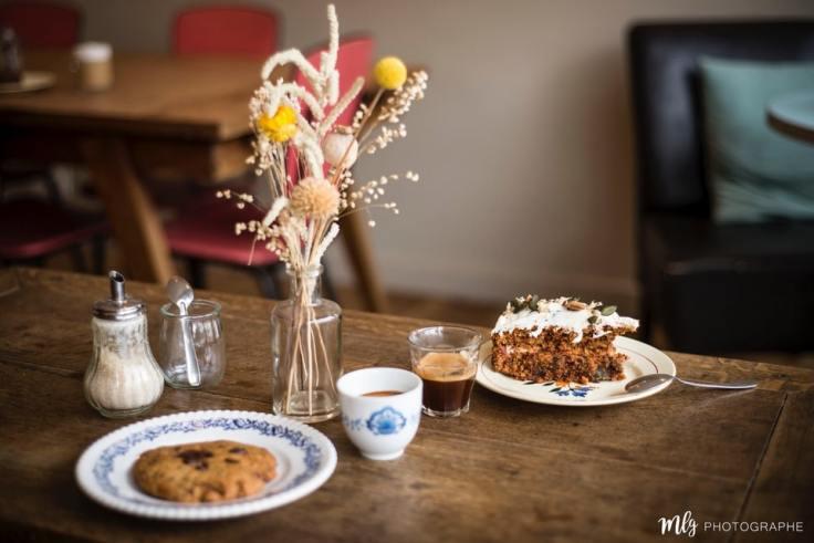 Une table décorée avec des fleurs , un café autour d'un cookie et d'un gâteau.