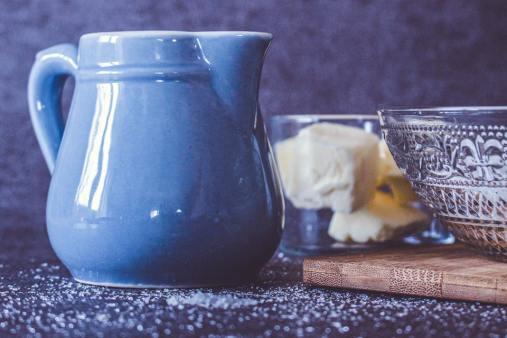 Tellière bleu ciel et verre contenant du beurre salé sur une table de cuisine
