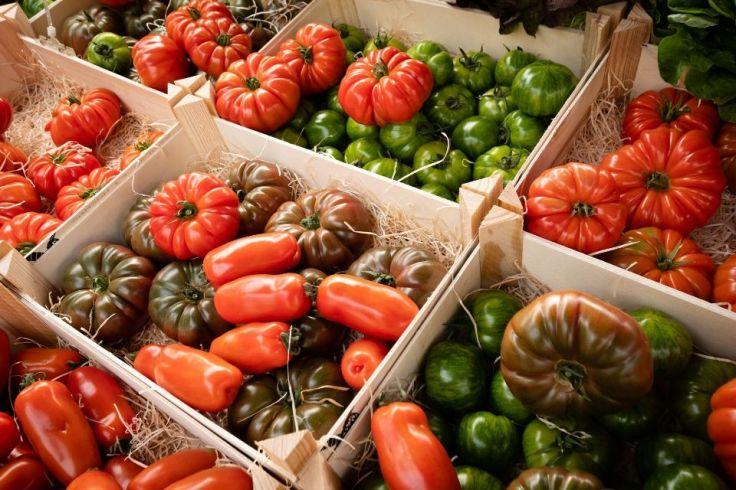Des légumes sont dans des palettes sur un stand de marché