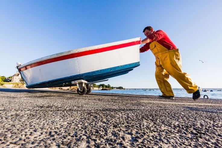 Un marin qui pousse son petit bateau breton