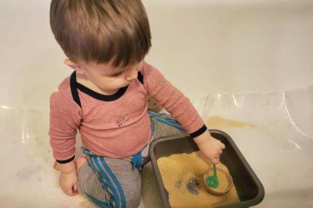 un enfant manipule la semoule avec la cuillère pendant l'activité transvasement.